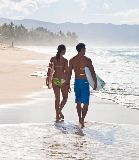 Hawaii couple surfboards walking beach